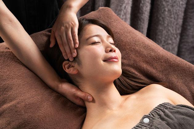 仰向けにで首の施術を受けている女性
